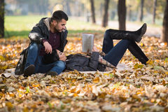 Couple Reading A Book During Autumn Stock Photo