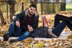 Couple Reading A Book During Autumn Stock Images