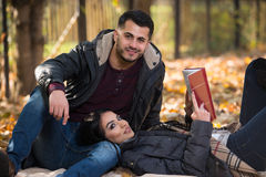Couple Reading A Book During Autumn Stock Photos