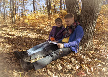 Couple reading book in autumn forest Stock Image