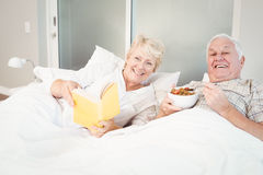 Couple reading book in bed at home Royalty Free Stock Images