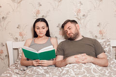 Couple reading a book in bed. Royalty Free Stock Photo