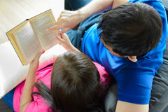 Couple reading book on the couch Royalty Free Stock Photos