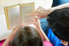 Couple reading book on the couch Stock Photo