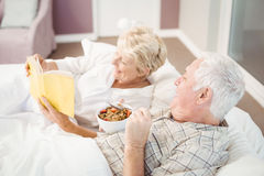 Couple reading book while having breakfast on bed Royalty Free Stock Photography