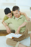 Couple reading book at home. Young couple resting at home couch, reading book, embracing Royalty Free Stock Photography