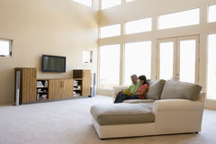 Couple reading book in living room Stock Image