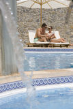Couple reading book in lounge chairs at poolside with fountain in foreground Stock Photo