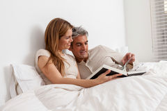 Couple reading a book lying in the bed Stock Images