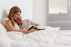 Couple reading a book lying in the bed Royalty Free Stock Photo