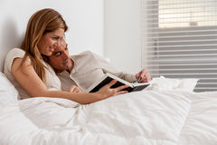 Couple reading a book lying in the bed Stock Photo