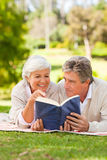 Couple reading a book in the park Stock Image