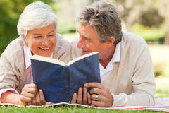 Couple reading a book in the park Stock Photography