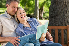 Couple reading book on park bench Royalty Free Stock Image
