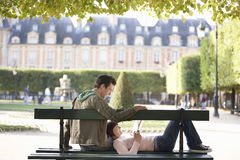 Couple Reading Book On Park Bench Stock Photos