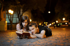 A couple reading book on a road Stock Photography