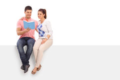 Couple reading book seated on a panel Royalty Free Stock Photos