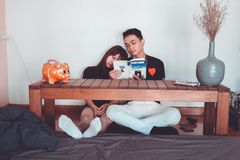 Couple Reading Book Sitting on Front of Rectangular Brown Wooden Coffee Table stock photo