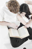 Couple reading book on a sofa Royalty Free Stock Photo
