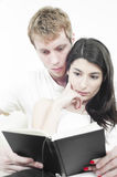 Couple reading book on a sofa Stock Photography
