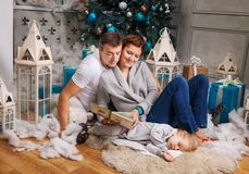 Couple reading book to son beside Christmas tree Stock Photography