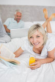 Couple reading book and using laptop in bed Royalty Free Stock Photo