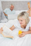 Couple reading book and using laptop in bed Royalty Free Stock Photos
