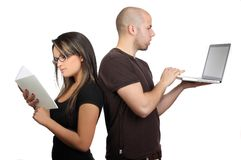 Couple reading book on working on laptop Royalty Free Stock Images