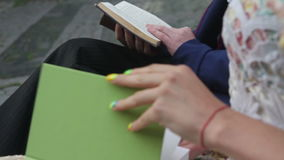 Couple reading a books on a bench stock video footage