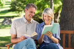 Couple reading books on bench Stock Photo