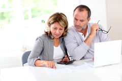 Couple reading construction plan and using laptop Royalty Free Stock Photography