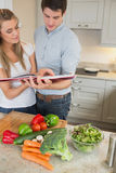Couple reading cookery book Royalty Free Stock Image