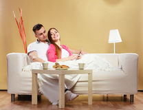 Couple reading ebook relaxing at home on sofa. Stock Photos