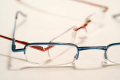 Couple of reading glasses. One red, one blue royalty free stock images