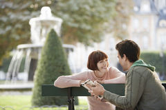 Couple Reading Guide Book On Park Bench Royalty Free Stock Image
