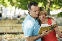Couple Reading Guidebook. Happy couple reading a guidebook outdoors stock photos