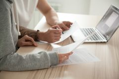Couple holding reading documents at home with laptop, close up. Couple reading legal documents at home with laptop, family conering mortgage loan or insurance stock image