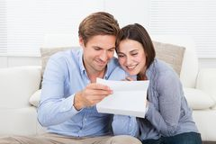 Couple reading letter at home Stock Photos