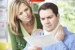 Couple Reading Letter In Respect Of Husband's Neck Injury. Worried Couple Reading Letter In Respect Of Husband's Neck Injury stock photo