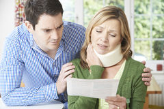 Couple Reading Letter In Respect Of Wife's Neck Injury. Couple Reading Letter Concerning Wife's Neck Injury Royalty Free Stock Photo