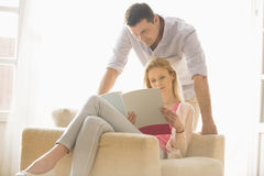Couple reading magazine together at home Royalty Free Stock Image