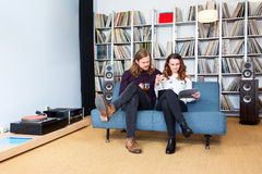 A couple reading a magazine together while listening to music Royalty Free Stock Photos