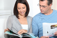 Couple reading magazines Royalty Free Stock Photos