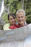 Couple Reading Map Against Waterfall Stock Image