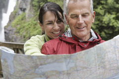 Couple Reading Map Against Waterfall Royalty Free Stock Photo
