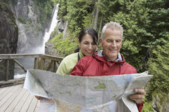 Couple Reading Map Against Waterfall Stock Photo