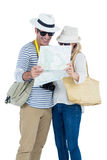 Couple reading map against white background. Front view of couple reading map while standing against white background Royalty Free Stock Photo