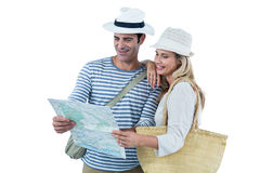 Couple reading map against white background. Mid adult couple reading map against white background Royalty Free Stock Photography