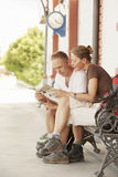 Couple Reading Map On Bench Royalty Free Stock Photography