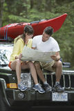 Couple Reading Map On Car Royalty Free Stock Images